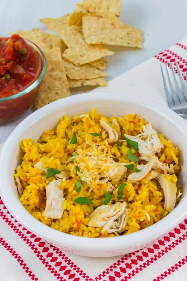 arroz con pollo that was cooked in the Instant Pot, served in a white bowl along with tortilla chips and salsa