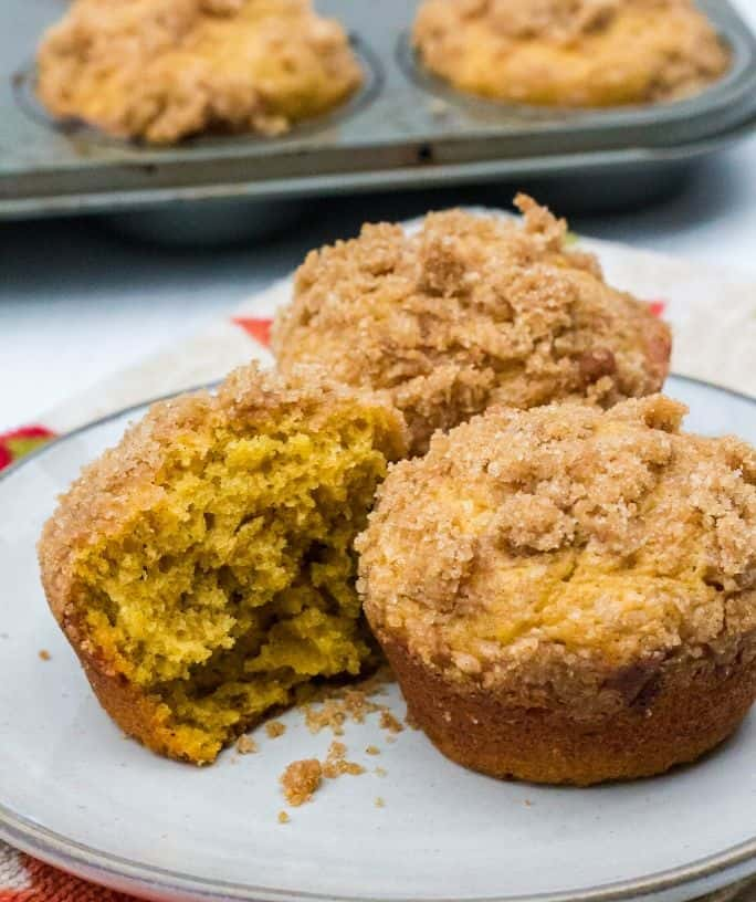 pumpkin banana muffins on a white plate, with one of the muffins cut in half