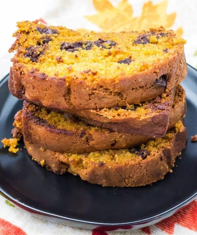 stacked slices of pumpkin chocolate chip bread on a black plate