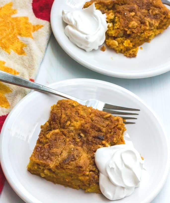 two slices of pumpkin crunch cake on white dessert plates