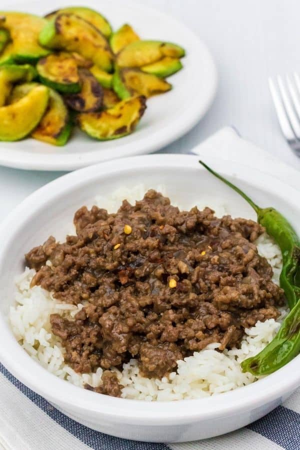 bowl of Instant Pot Korean ground beef and rice, garnished with shishito peppers