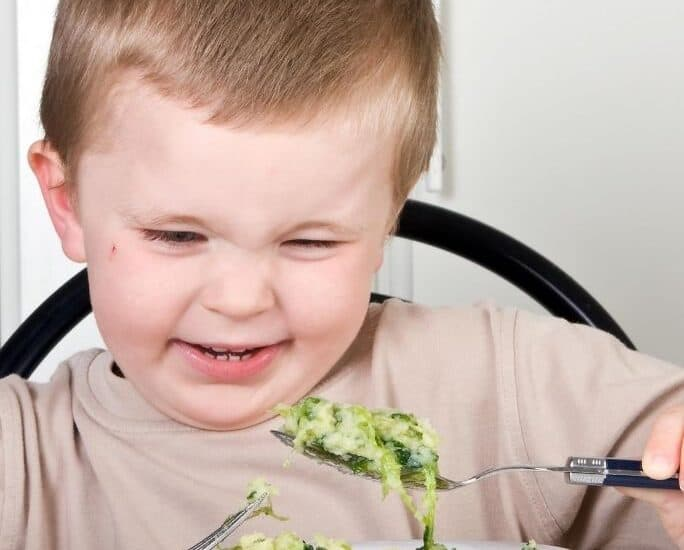 young boy grimacing at a plate of broccoli