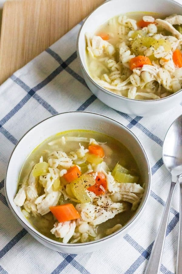two white bowls of chicken barley soup on a blue and white checked napkin