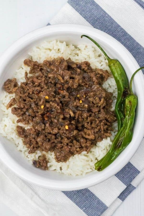 white bowl filled with rice and Korean ground beef that were both cooked in the Instant Pot, served with shishito peppers.