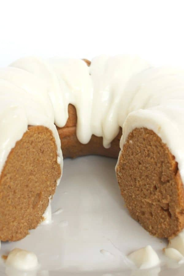 Instant Pot pumpkin bundt cake with a slice removed from it, topped with cream cheese frosting
