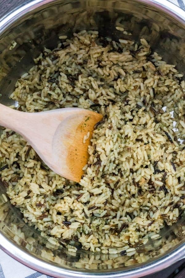 Instant Pot wild rice that has just been cooked, with a wooden spoon in the insert pot for serving.