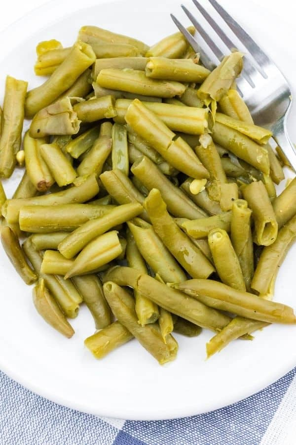 southern style canned green beans cooked in the Instant Pot, on a white plate with a fork in them