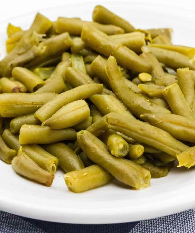white plate piled with a helping of canned green beans cooked in the pressure cooker