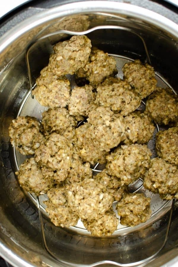 frozen meatballs that have been cooked in the Instant Pot, resting on the trivet in the insert pot, ready to be drained