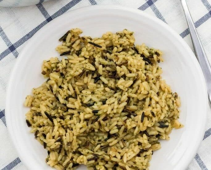 white plate of wild rice cooked in the pressure cooker, on a blue and white napkin