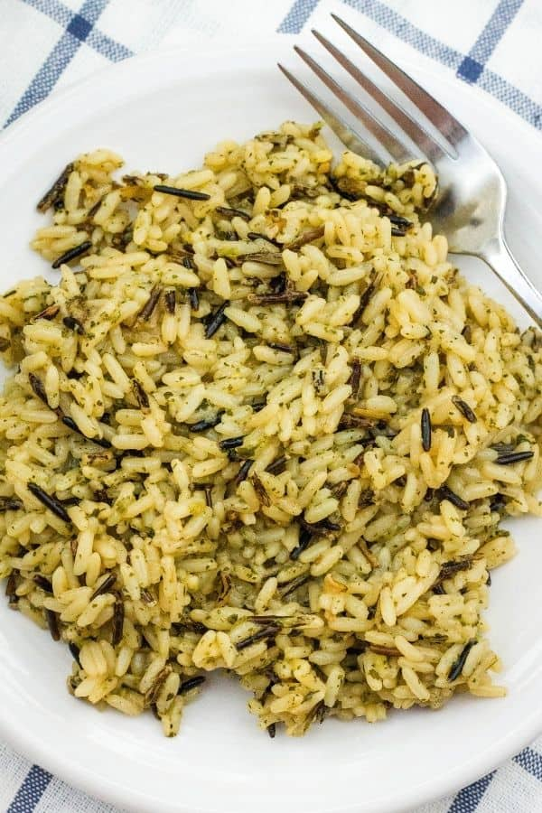 A heaping helping of wild rice cooked in the pressure cooker, on a white plate with a fork