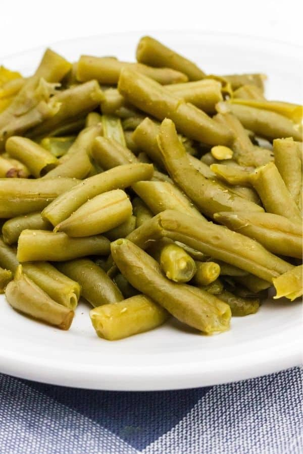 a white plate with a helping of homestyle green beans cooked in the Instant Pot from a can.