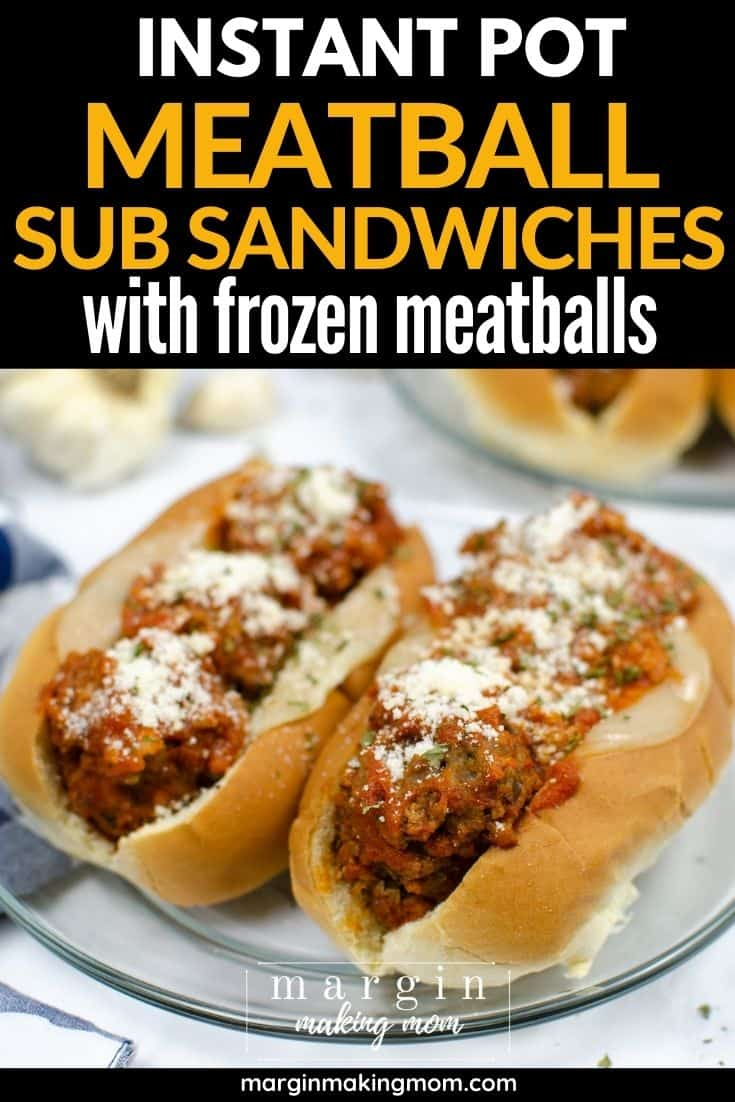 two meatball subs on a clear glass plate, each topped with grated parmesan cheese