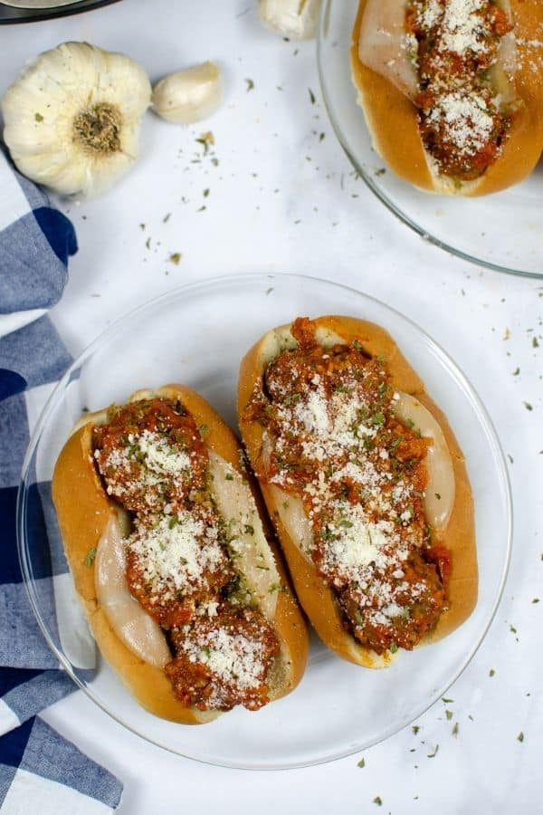 aerial view of two Italian meatball subs on a clear glass plate, next to a blue and white checkered napkin, with the Instant Pot in the background