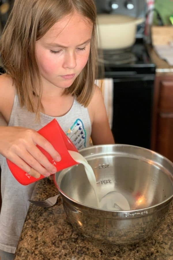 Female child pouring milk into a mixing bowl.