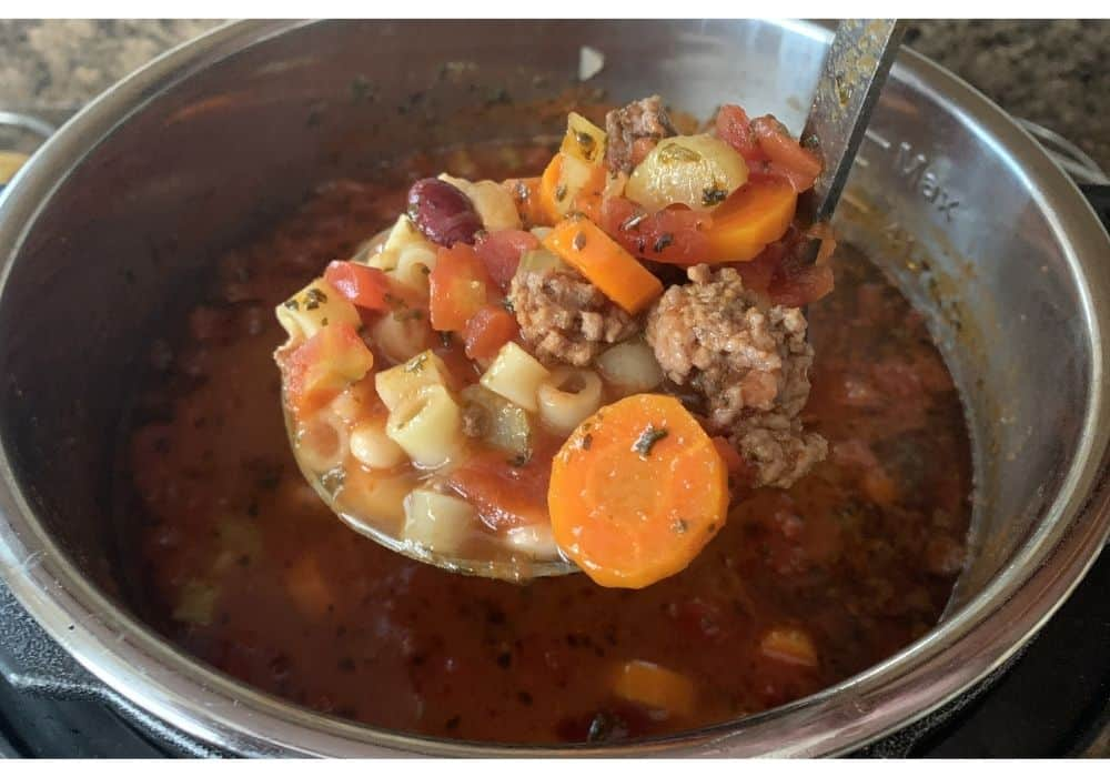 a ladle scooping out pasta e fagioli in the Instant Pot