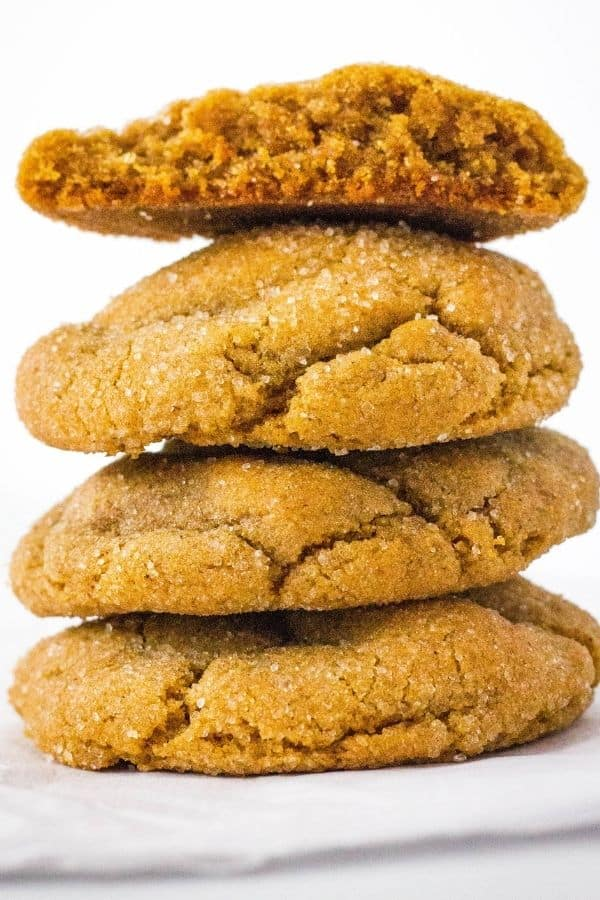 stack of four old-fashioned ginger molasses cookies, with the top cookie broken in half to show the interior.
