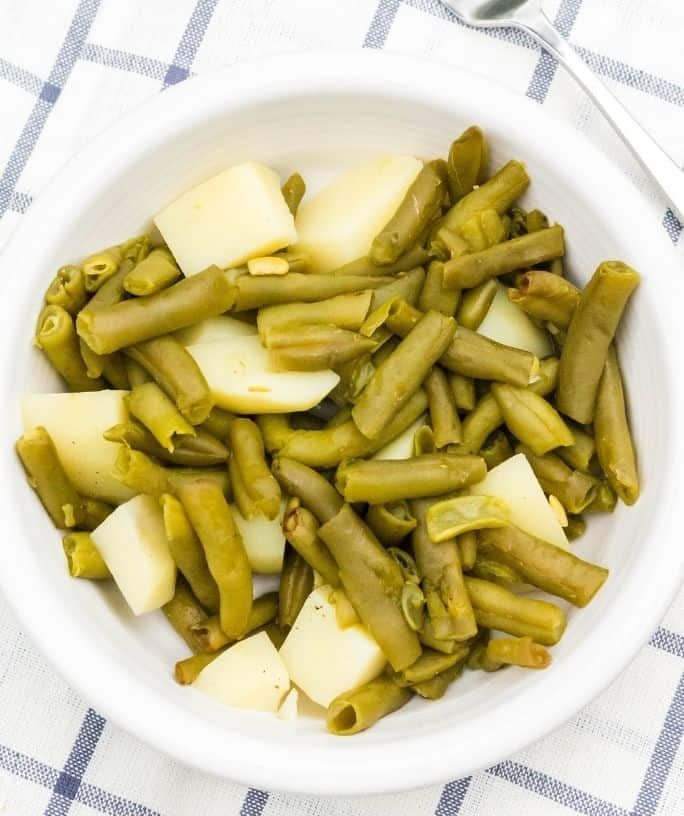 cooked canned green beans and potatoes are in a white bowl on a blue and white cloth, after being cooked in the pressure cooker