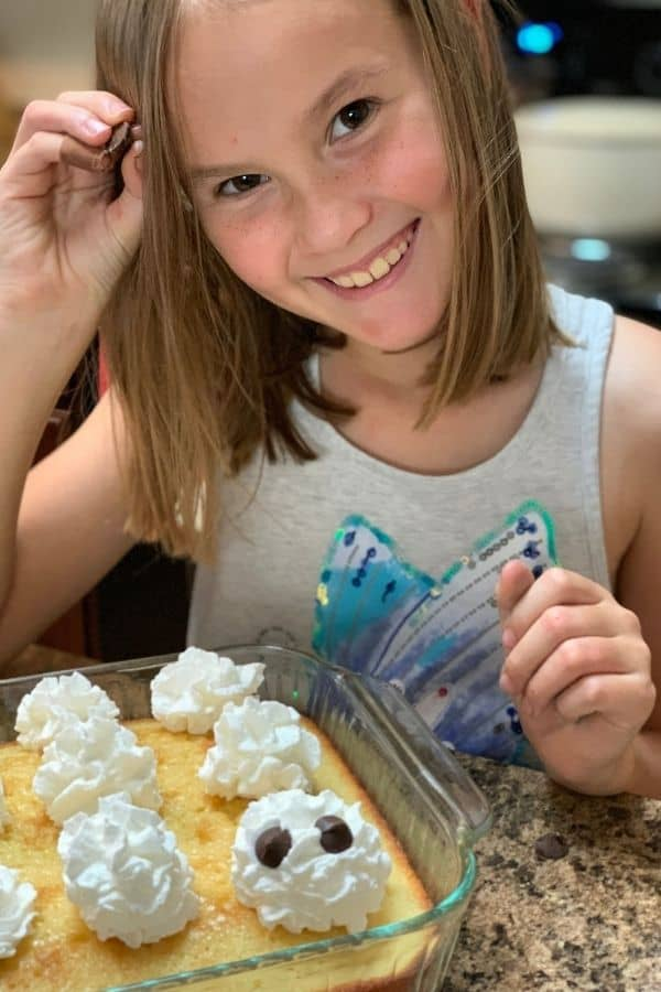 Child smiling while decorating tres leches cakes to look like ghosts.