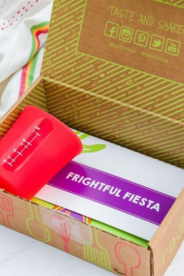 """Raddish Kids box containing a red silicone liquid measuring cup as well as a packet titled """"Frightful Fiesta."""""""