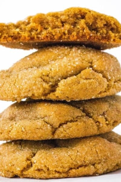 stack of four molasses sugar cookies, with the top cookie broken in half to show the soft inside.