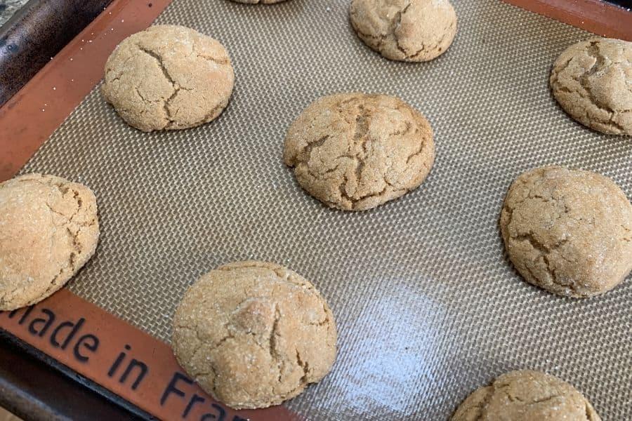 Freshly baked molasses cookies on a baking sheet.