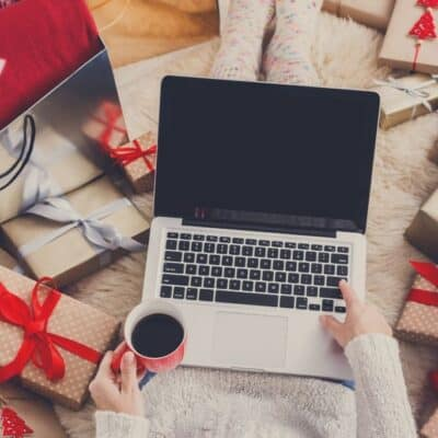 woman shopping on her laptop while holding a cup of coffee, with multiple Christmas presents surrounding her