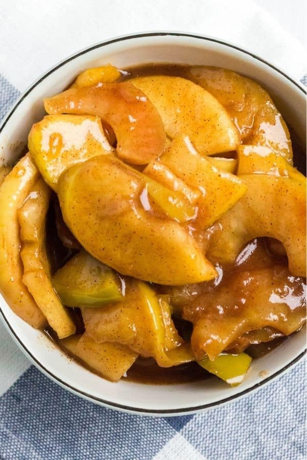 A serving of tender pressure cooker cinnamon apples in a cream-colored bowl.