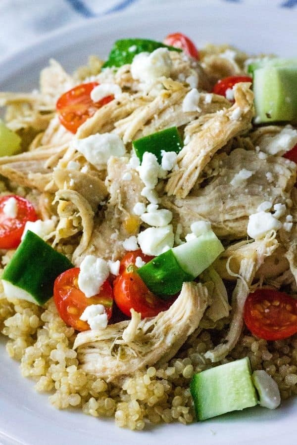 Quinoa, Greek chicken, cucumbers, tomatoes, and feta served on a white plate