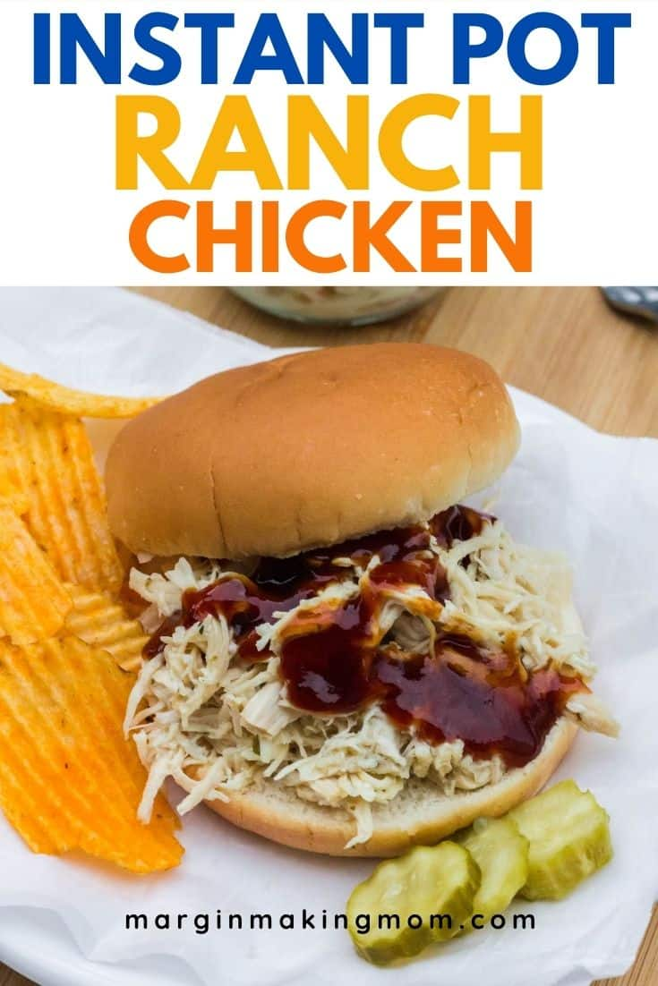 ranch chicken on a bun, topped with BBQ sauce, next to chips and pickle slices.