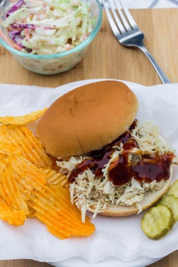 piece of parchment paper with a ranch chicken sandwich on it, as well as some potato chips, pickle slices, and a glass bowl of coleslaw.