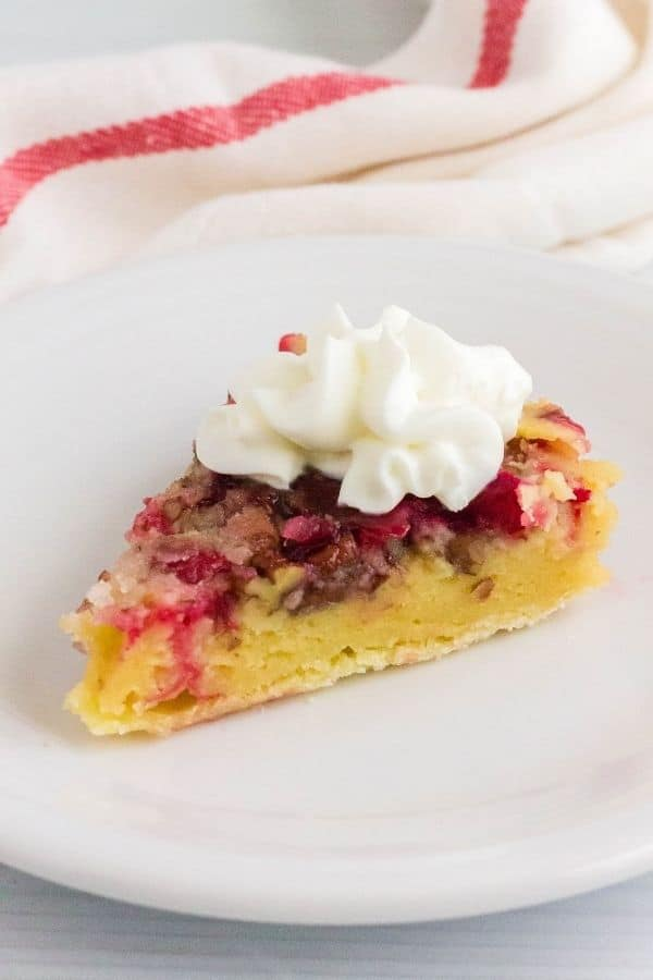 side view of a slice of Nantucket cranberry pie on a white plate, topped with whipped cream