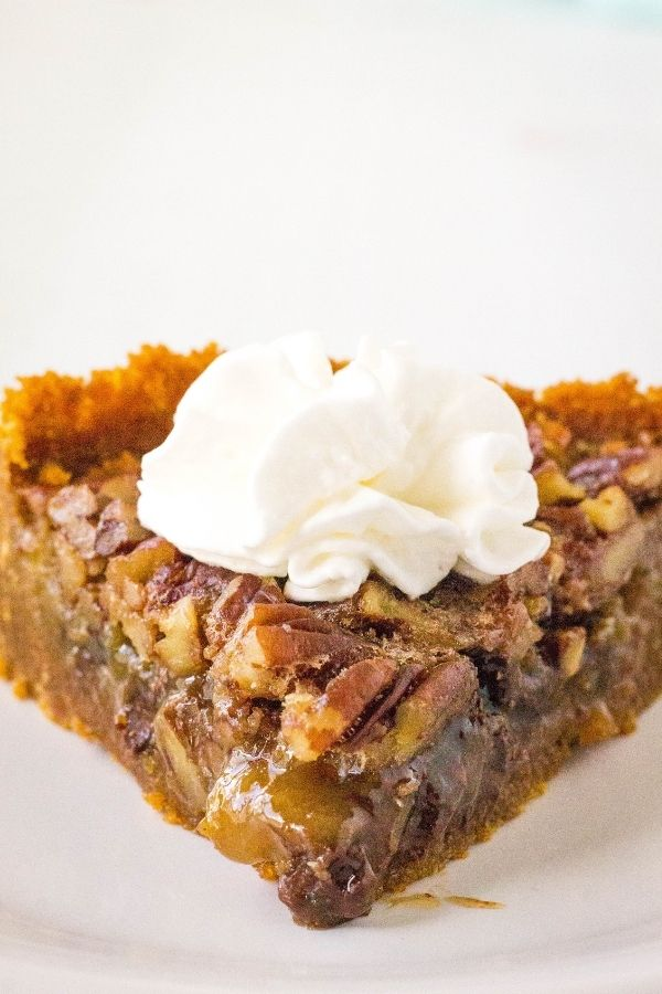 a head-on view of a slice of pressure cooker pecan pie with a dollop of whipped cream on top