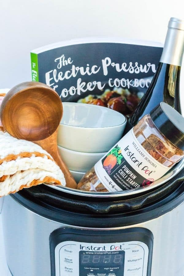 Soup-themed Instant Pot gift basket, filled with a soup starter mix, hand towel, ladle, soup bowls, and cookbook.