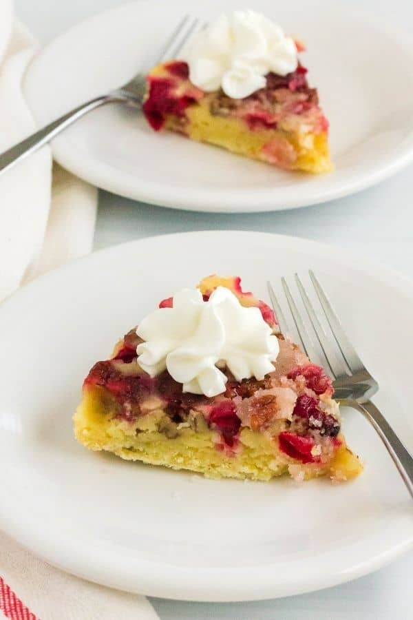 two white plates, each serving a slice of Instant Pot cranberry pie topped with whipped cream, with forks next to each slice