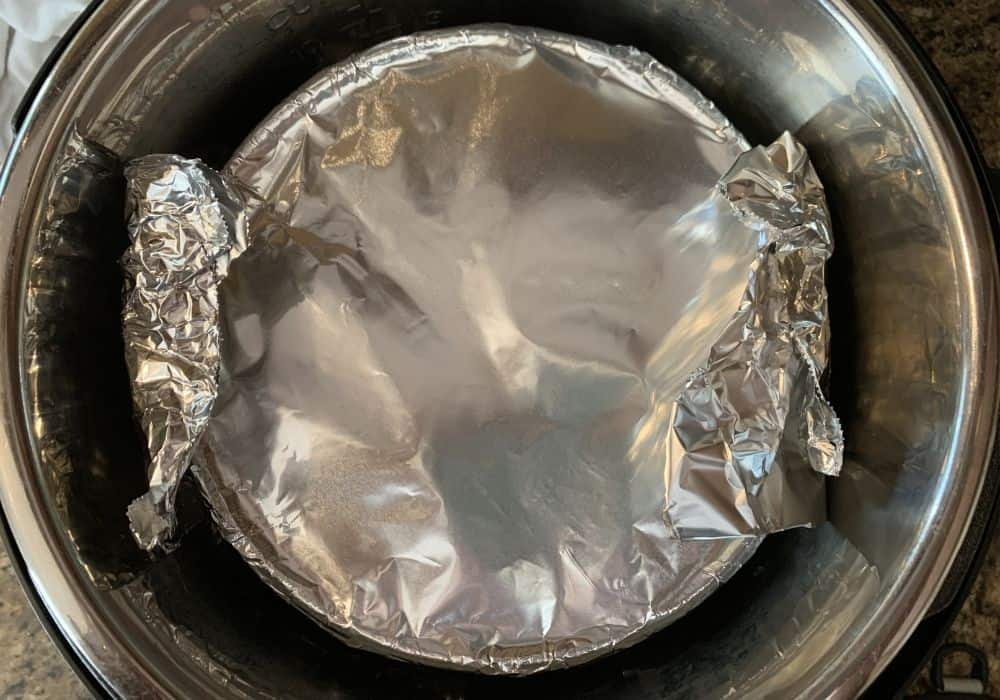 pecan pie in the insert pot of the Instant Pot, covered with foil for cooking.