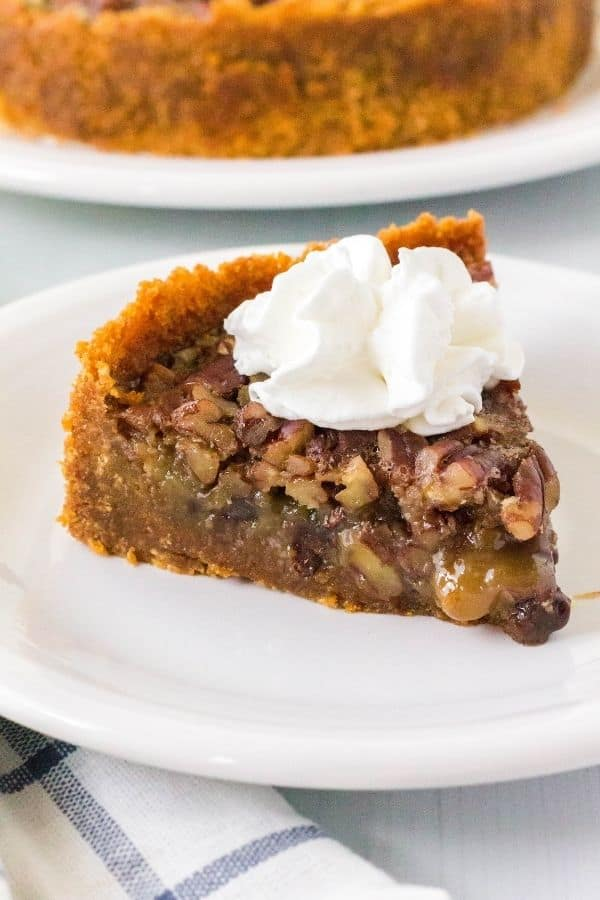 A slice of Instant Pot pecan pie with chocolate chips topped with whipped cream on a white plate, with the rest of the pie in the background.