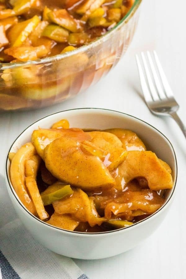 a cream-colored bowl filled with Instant Pot fried apples, with a serving bowl full of cinnamon apples in the background
