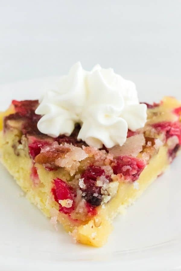 Close-up view of a slice of pressure cooker cranberry pie topped with whipped cream