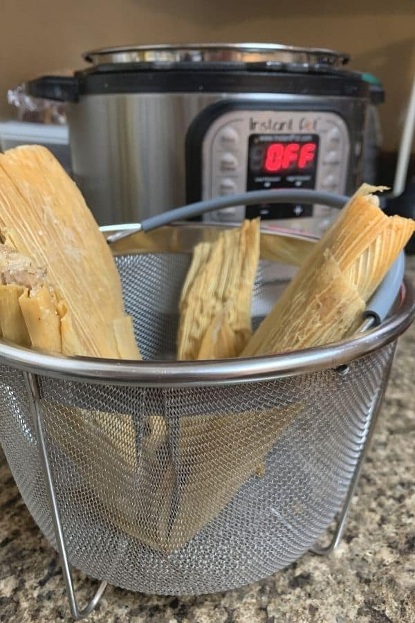 tamales standing upright in a steamer basket