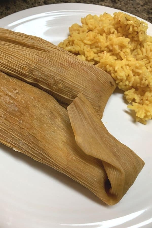 two tamales that were reheated in the Instant Pot, next to a serving of yellow spanish rice