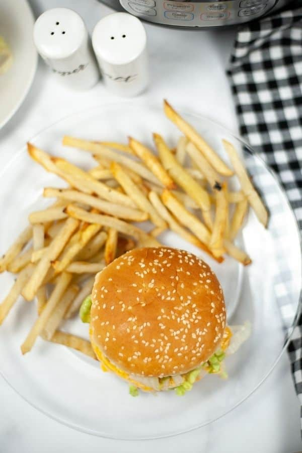 overhead view of an Instant Pot burger with fries on a clear glass plate