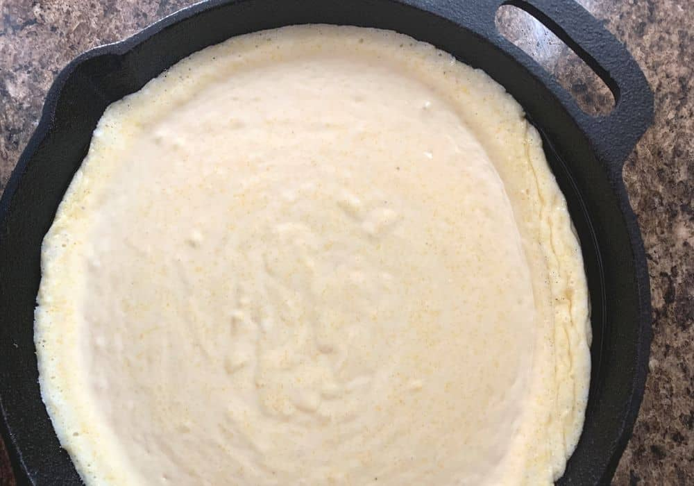 Jiffy cornbread batter in a cast iron skillet, ready to be baked.