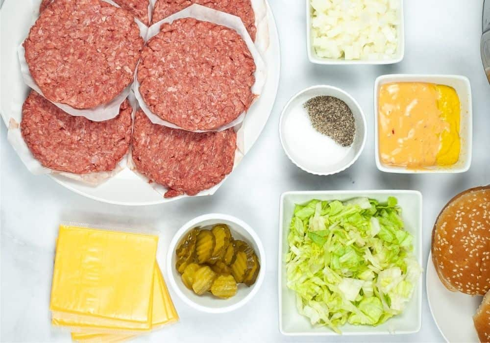 a plate of raw hamburger patties for making burgers in the Instant Pot, plus various toppings including cheese, pickles, lettuce, salt, pepper, dressing, onions, and buns.