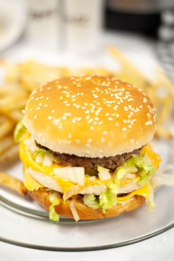 a double cheeseburger cooked in the Instant Pot served on a clear glass plate with a side of french fries
