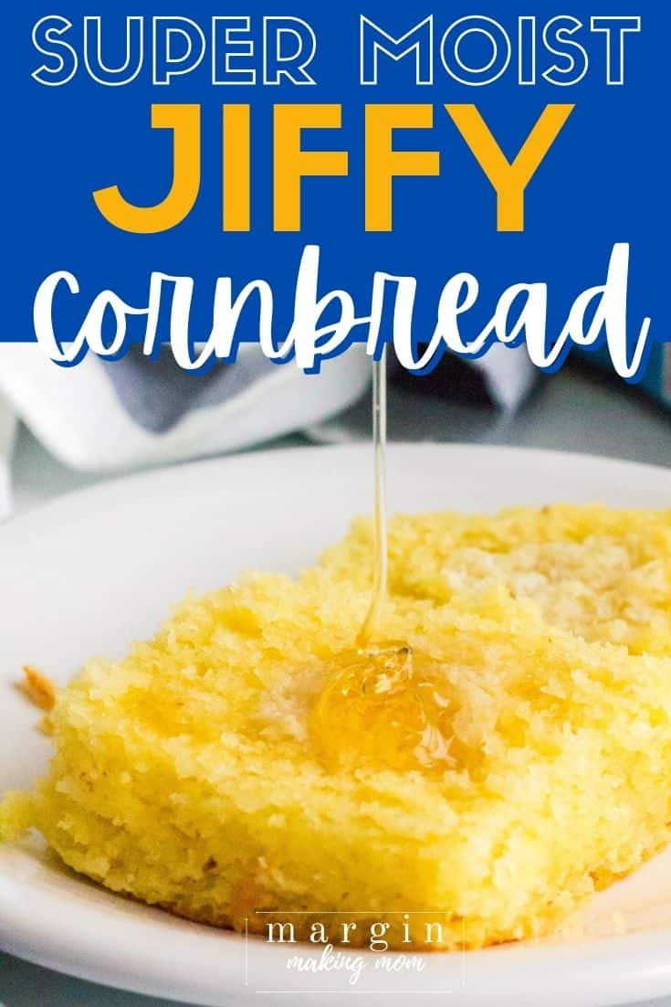 a piece of moist JIffy cornbread on a white plate, with honey being drizzled on top.