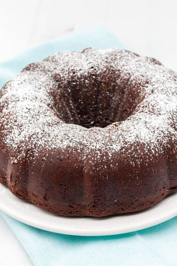 Whole chocolate bundt cake dusted with powdered sugar, served on a white plate.