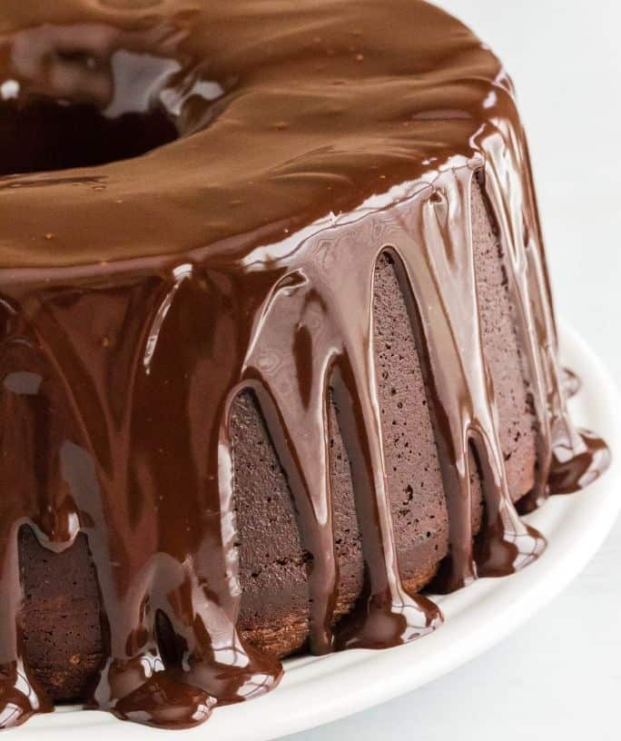 chocolate pound cake made with sour cream, topped with chocolate ganache and served on a white plate