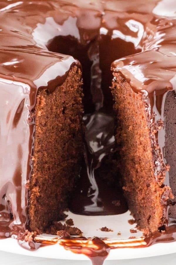 chocolate sour cream pound cake with a slice removed, showing the moist interior and the ganache flowing through.