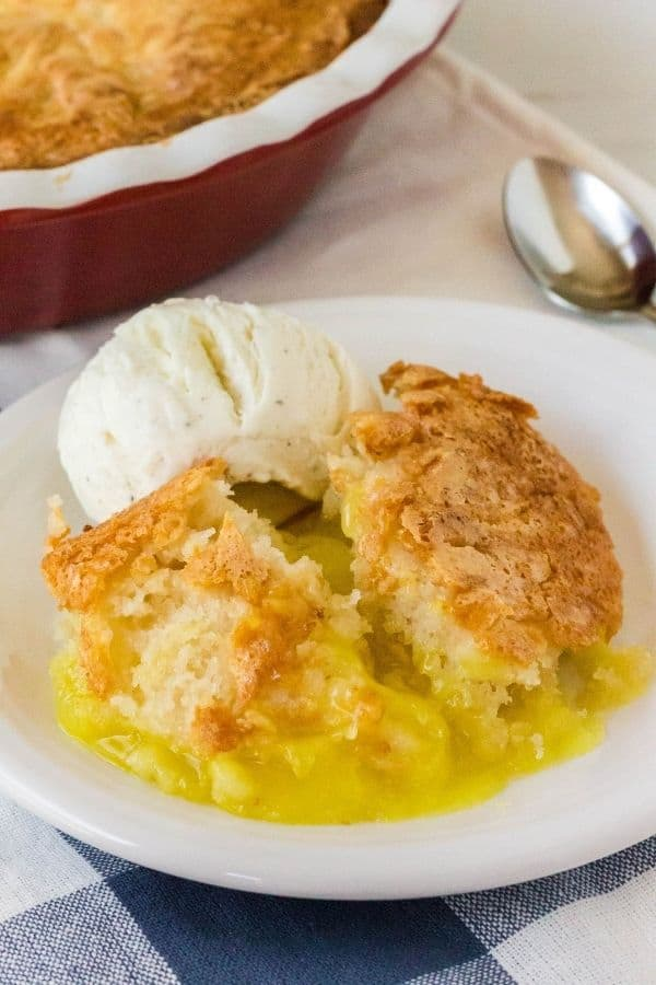 lemon cobbler on a white plate with a scoop of vanilla ice cream, atop a blue and white checked napkin